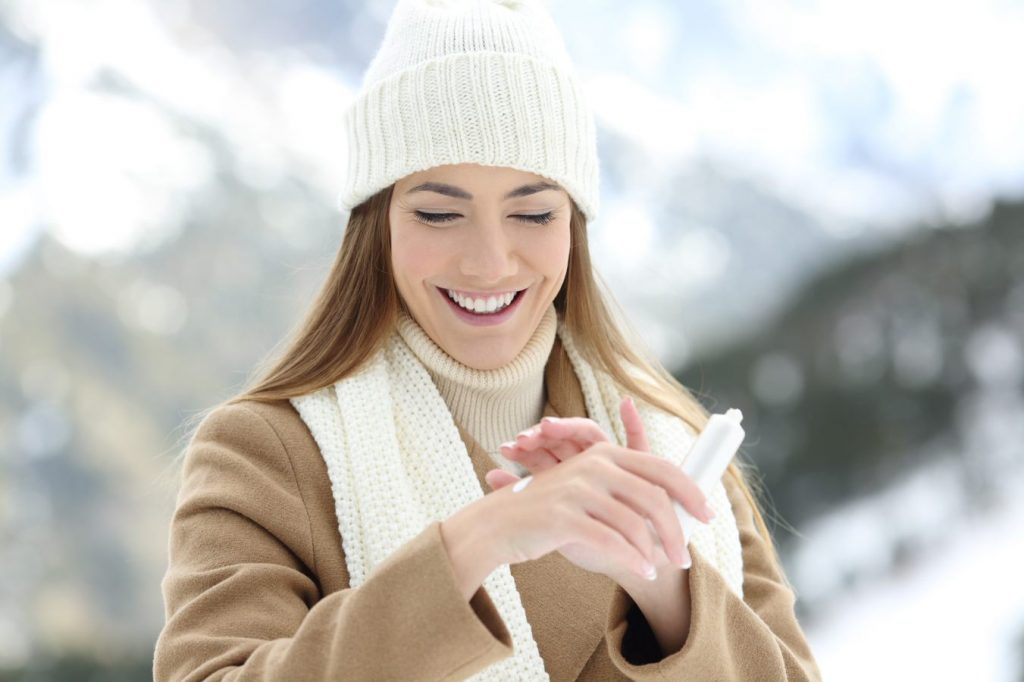 Smiling woman in snow applies lotion to her hands.