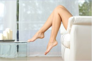 Woman sitting on couch with foot on glass table