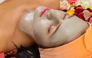 woman lying on her back with deep pore cleansing facial mask