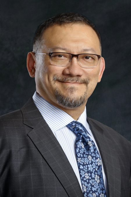 Head shot of Dr. Tu, who is wearing a charcoal suit, blue and white pinstriped shirt, and blue floral tie