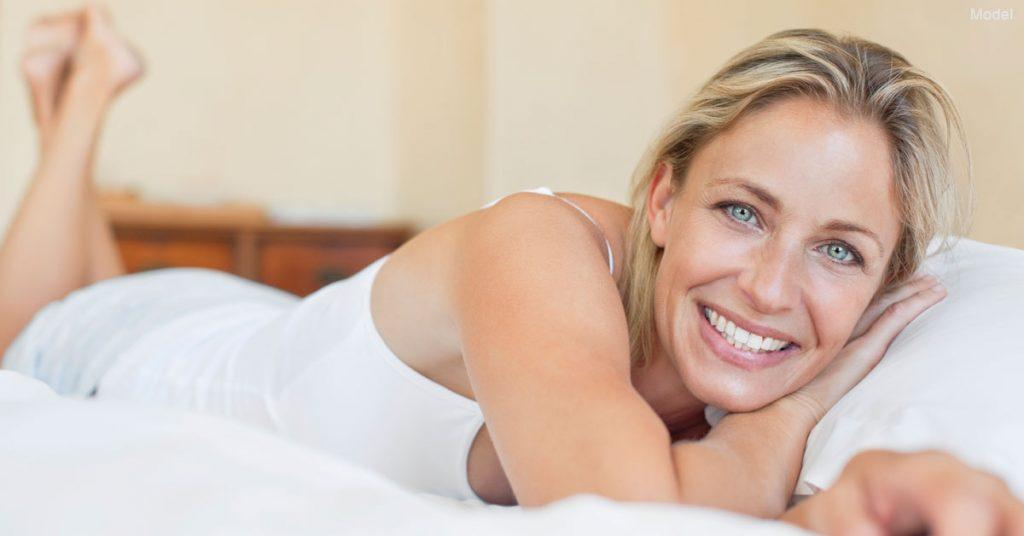 Woman with smooth youthful skin lying on bed